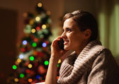 Happy young woman talking cell phone in front of christmas tree — Stock Photo