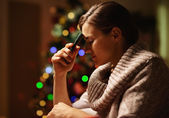 Concerned young woman with mobile phone in front of christmas tr — Stock Photo