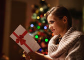 Happy young woman reading postcard in front of christmas tree — Stock Photo