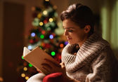 Happy young woman reading book in front of christmas tree — Photo