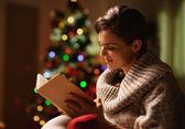 快乐的年轻女人阅读本书前的圣诞树 — 图库照片
