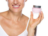 Closeup on young woman showing cream bottle — Stock Photo