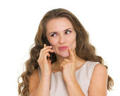 Portrait of thoughtful young woman talking mobile phone — Stock Photo