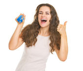 Happy young woman showing keys and thumbs up — Stock Photo