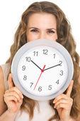 Jonge vrouw achter klok verbergen — Stockfoto