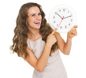 Smiling young woman pointing on clock — Stock Photo