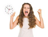 Stressed young woman with clock — Stock Photo