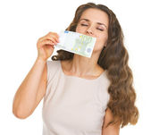 Young woman sniffing 100 euros banknote — Stock Photo