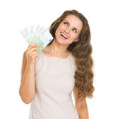 Happy young woman with euros looking up on copy space — Stock Photo