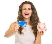 šťastná mladá žena ukazují kreditních karet a prasátko — Stock fotografie