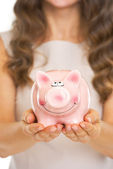 Closeup on piggy bank in hand of young woman — Stock Photo