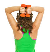 Fitness young woman making exercise with dumbbells . rear view — Fotografia Stock