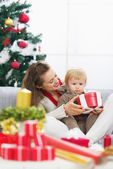 Happy mother showing baby christmas present box — Stock Photo