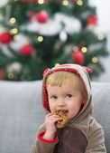 Portrait of happy baby in christmas costume eating cookie — Stock Photo