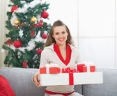Portrait of happy young woman with christmas present boxes near — Stock Photo
