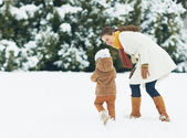 Happy mother and baby walking outdoors in winter — Stock Photo