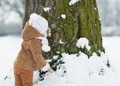 Barnet leker med träd på vintern. bakifrån — Stockfoto