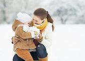 Madre y bebé jugando en el parque de invierno — Foto de Stock