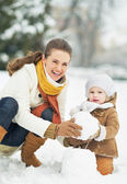 Happy mother and baby making snowman in winter park — Stock Photo