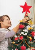 Happy young woman setting top on christmas tree — Stock Photo