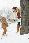 Happy mother playing with baby in winter outdoors — Foto Stock