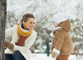 Happy mother playing with baby in winter park — Stock Photo