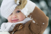 Portrait of happy baby looking out from hat in winter park — Stock Photo