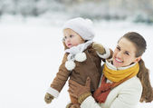 Happy mother holding baby looking on copy space in winter park — ストック写真