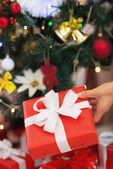 Closeup on christmas present box on christmas tree background — Stock Photo