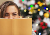 Happy young woman hiding behind book near christmas tree — Stock Photo