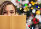 快乐的年轻女人,躲在附近的圣诞树的书 — 图库照片