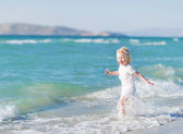 Happy baby running into sea — Stock Photo