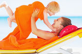 Happy mother and baby playing on chaise-longue — Stock Photo