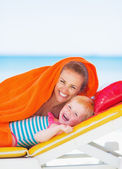 Portrait of smiling mother and baby laying on sunbed — Stock Photo