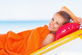 Lachende jonge vrouw opleggen zonnebank — Stockfoto
