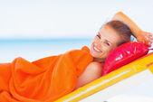 微笑着的年轻女子躺在日光浴浴床 — 图库照片