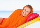Jovem mulher envolvida em toalha deitado na espreguiçadeira a sorrir — Fotografia Stock