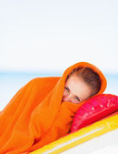Young woman wrapped in towel laying on sunbed — Photo