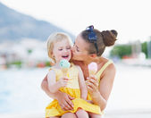 Mother kissing baby while eating ice cream — Stock Photo