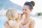 Vlekkerig moeder en baby eten van ijs — Stockfoto