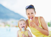 Happy mother and baby eating ice cream — Stock Photo