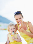 Smiling mother and baby eating ice cream — Stock Photo