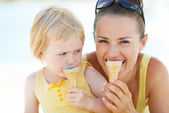 Mother and baby biting ice cream — Stockfoto