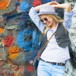 Stock Photo: Smiling hipster girl against urbwall