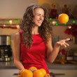 Happy young womthrowing up orange in christmas — Stock Photo #33775451