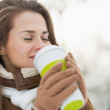 Happy young woman holding cup of hot beverage in winter outdoors — Stock Photo
