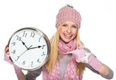 Smiling girl in winter clothes pointing on clock — Stock Photo