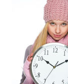 Girl in winter clothes showing clock — Stock Photo