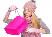Curious girl in winter clothes looking into shopping bag — Stock Photo