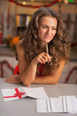 Thoughtful young housewife signing christmas postcards — Stock Photo